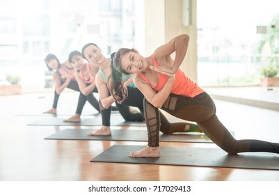 fitness, sport, training, yoga and people concept - Asian woman stretching in gym.Group Of female Doing Yoga Indoors. Asana yoga pose