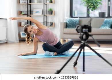 fitness, sport and video blogging concept - woman or blogger with camera streaming online yoga class at home