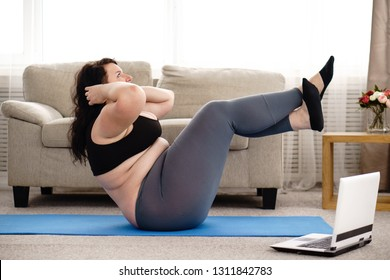fitness, sport, weight loss, exercising, home workout, training, lifestyle. young plus size woman doing sit-ups on mat at home