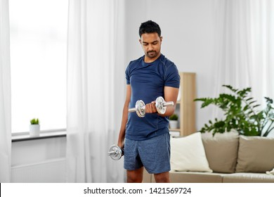 fitness, sport, weightlifting and bodybuilding concept - indian man exercising with dumbbells at home