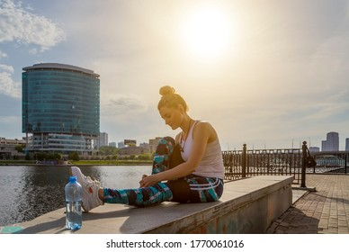 Fitness sport woman in fashion sportswear doing yoga fitness exercise in city street . Outdoor sports clothing and shoes, urban style. Tie sneakers