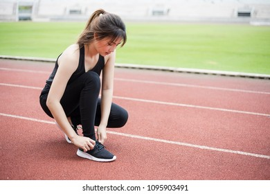Fitness sport woman tying shoes rope.