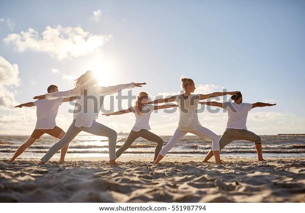 Fitness, Sport, Yoga und gesunder Lebensstil - Gruppe von Menschen, die Krieger am Strand stellen
