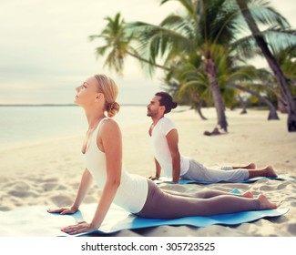 fitness, sport, yoga, people and lifestyle concept - happy couple making yoga exercises on tropical beach