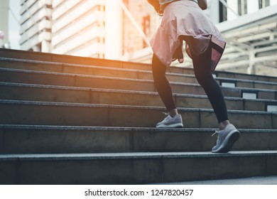 fitness, sport,exercising and lifestyle concept.Stretching outdoors. Low angle view of Sporty young woman training outdoors.sporty woman running onsteps at early morning jogging on city stairs.