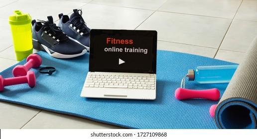 Fitness sports equipment and laptop on gray cement background. Home online workout concept. Fitness online training.