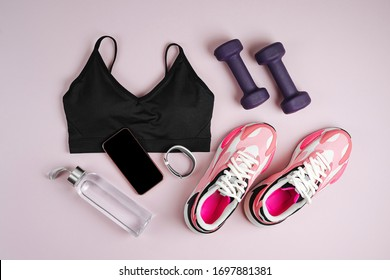 Fitness sports equipment and sneakers on a pink background.  Online Fitness program. Home online workout. Top view, flat lay