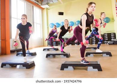 Fitness, deportes, entrenamiento, gimnasia y concepto de estilo de vida - un grupo de mujeres trabajando con pisapeantes en el gimnasio.