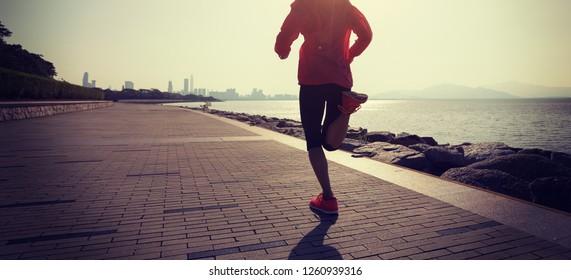 Fitness sportswoman running on sunny coast road