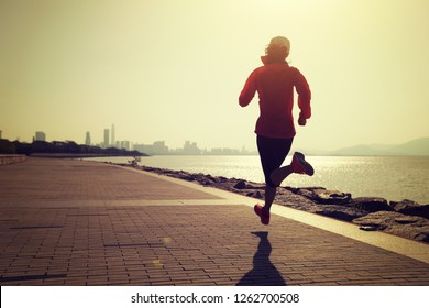Fitness sportswoman running on sunny coast road with modern city in the distance