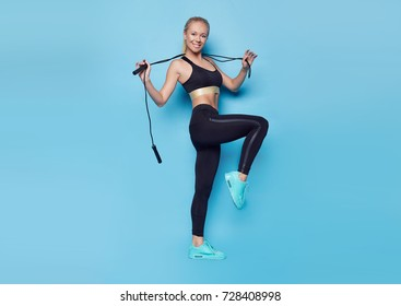 Fitness sporty blond woman posing at studio holding jump rope. Beautiful fit Girl. Fitness model in sportswear. Weight Loss. Healthy lifestyle. Sporty healthy female.