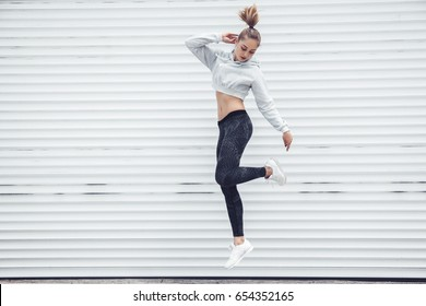 Fitness sporty girl in fashion sportswear dancing hip hop in the street, outdoor sports, urban style. Teen model in swag clothes posing outside.