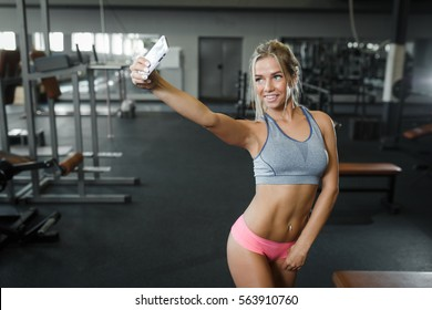 Fitness sporty sexy blond girl making selfie photo on smartphone during workout break