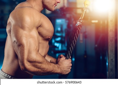 Fitness strength training workout bodybuilding concept background - muscular bodybuilder handsome man doing exercises in gym naked torso on diet