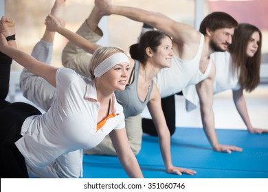 Fitness, stretching practice, group of four attractive smiling fit young people working out in sports club, doing kneeling kickbacks, exercise for lower back, hips and buttocks in class