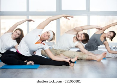 Fitness, stretching practice, group of four beautiful happy fit young people working out in sports club, doing side bend exercise, Revolved Head to Knee pose on blue mats in class