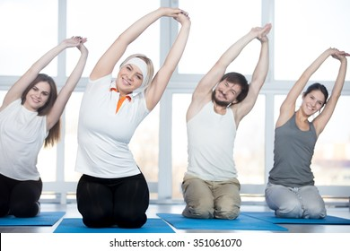 Fitness, stretching practice, group of four beautiful happy fit young people working out in sports club, doing side bend exercises with raised arms on blue mats in class