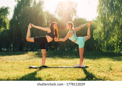 Fitness, stretching practice, group of two attractive women doing yoga. Wellness concept.