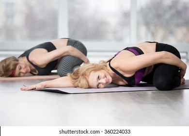 Fitness, stretching practice, group of two attractive happy smiling fit mature women working out in sports club, doing Frog Yin Yoga Pose, Mandukasana posture in class, full length