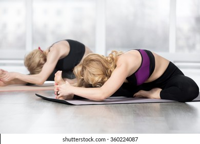 """Fitness, stretching practice, group of two attractive fit mature women working out in sports club, """"warming up"""", doing Head to Knee forward bend, Janu Sirsasana posture in class, full length"""