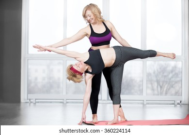 Fitness, stretching practice, group of two attractive fit senior women working out in sports club, instructor helping female student to do asana Ardha Chandrasana (Half Moon Pose) in class