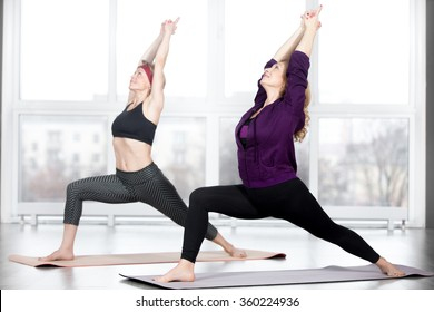Fitness, stretching practice, group of two attractive happy smiling fit mature women working out in sports club, doing Warrior 1 posture, Virabhadrasana I pose in class, full length