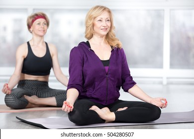 Fitness, stretching practice, group of two attractive fit happy senior females in sportswear working out in sports club, sitting in Easy (Pleasant Posture), Sukhasana, on meditation session in class