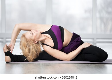 Fitness, stretching workout, attractive mature happy woman in violet sportswear working out in sports club, keeping fit, doing Revolved Head to Knee pose, Parivrtta Janu Sirsasana posture in class