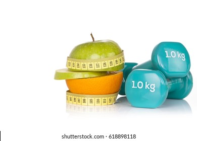 Fitness symbols - sliced apple and orange wrapped with yellow measuring tape with two blue vinyl coated dumbbells on white background