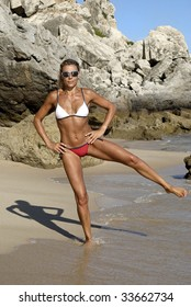 Fitness teacher in the beach showing some exercises