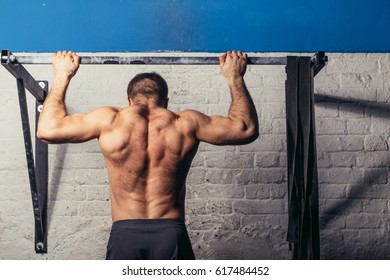 Fitness toes to bar man pull-ups bars workout exercise at gym