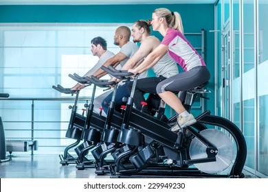 Fitness together on bicycles. Four friends pedal on a stationary bike at the gym