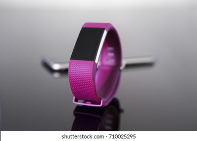 Fitness tracker close-up with smart phone on reflective glass