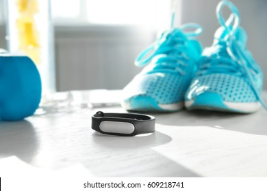 Fitness tracker and equipment on wooden table