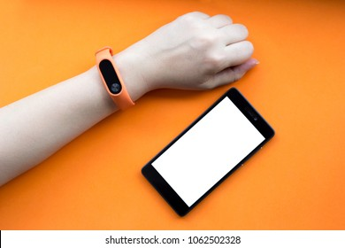 Fitness tracker on a female hand on an orange background and mock up of smartphone.