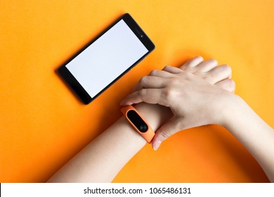 Fitness tracker on a woman hand on an orange background and mock up of smartphone.