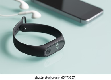 Fitness tracker, smartphone and earphones on green glass background.