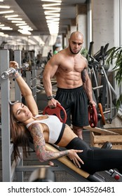 Fitness trainer controlling how young woman doing exercise