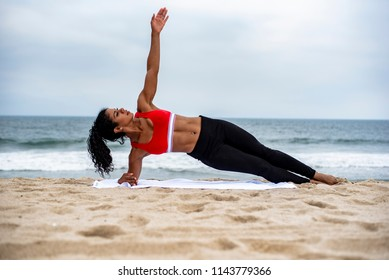 A fitness trainer does a side plank while exercising at the beach
