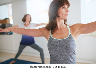 Fitness trainer doing the warrior pose during yoga class. Yoga teacher performing Virabhadrasana position in gym with people n background.