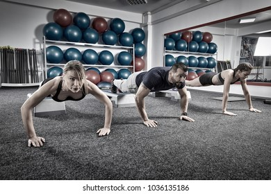 Fitness trainer and girls doing pushups in the gym