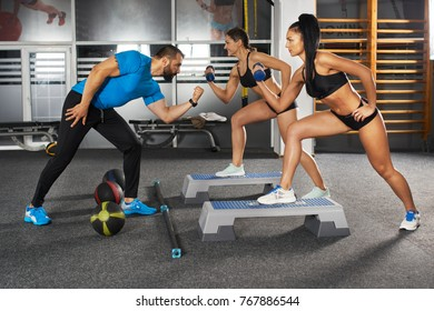 Fitness trainer and girls doing workout in the gym