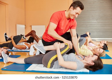 Fitness trainer helping with gymnastics exercise during pilates class