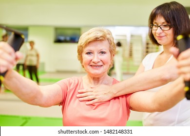 Fitness trainer or physiotherapist helps senior woman with sling training for the back
