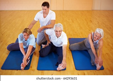 Fitness trainer showing stretching exercises to a group
