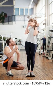 Fitness trainer showing thumb up to female client. Young excited woman celebrating her weight loss standing on scale at gym. Fitness achievements with a personal trainer.