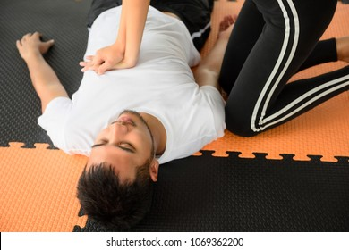 Fitness trainer woman giving cardiopulmonary resuscitation or CPR (life saving techniques) to heart attack drowning or heat stroke man in sport club. Urgent accident for Healthcare safety concept.