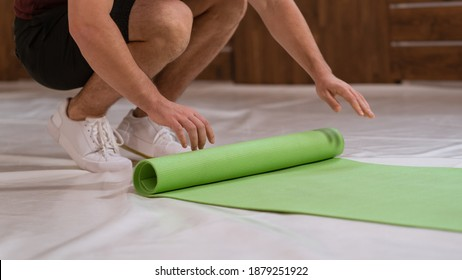 Fitness trainer young man, an athlete, unwinds a roll mat, preparing a place for sports. Determined guy doing physical training.
