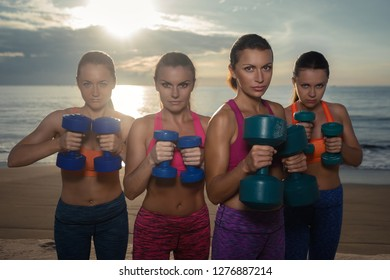 Fitness, training, aerobics and people concept - group of girls working out with dumbbells on the beach
