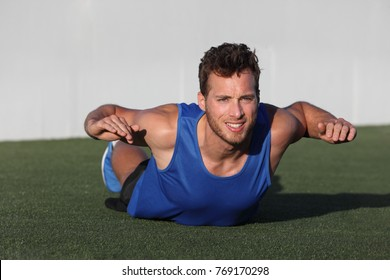 Fitness training back fat exercise fit man doing superman variation of lower body workout. Strong athlete working out outdoors in park grass. Lower body back lumbar muscles strengthening exercises.